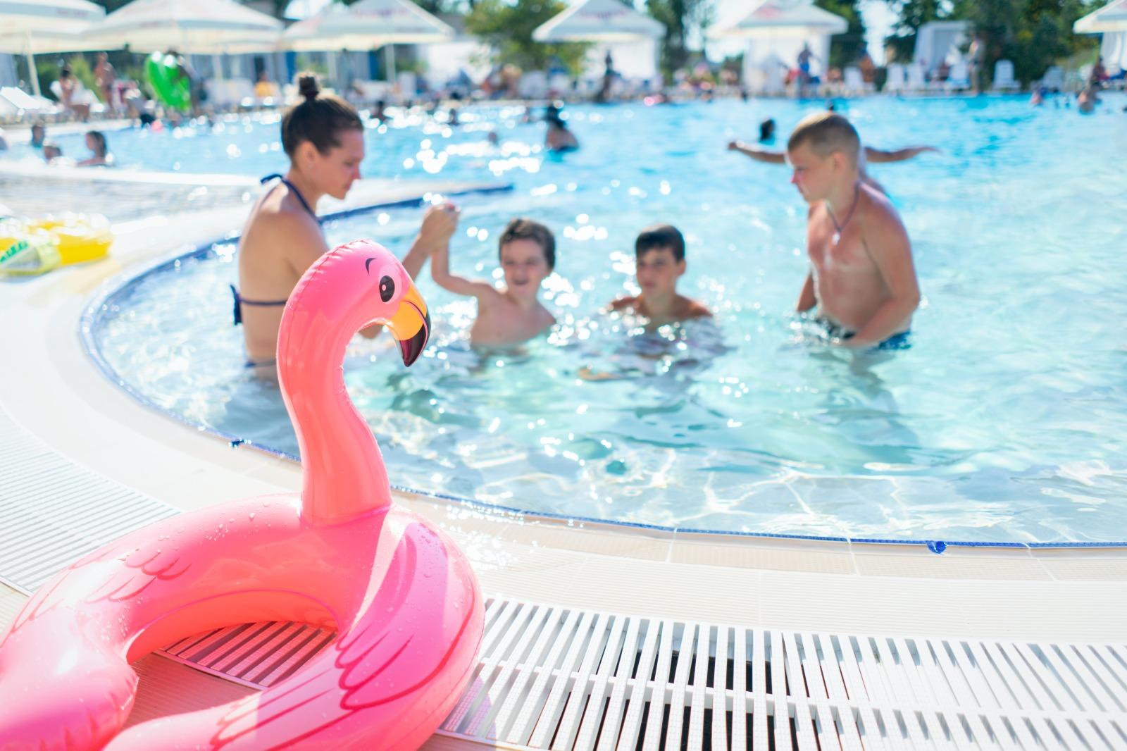 Foto, l'immagine ritrae una piscina rotonda con tanta gente. in primissimo piano un salvagente a forma di airone rosa poggiato sul bordo piscina. dietro, in secondo piano col viso sfocato, due bambini, un ragazzino e la mamma che giocano insieme